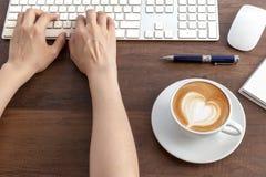 En dactylographiant et ayez une tasse de café de forme de coeur d'art de latte sur en bois Photo libre de droits