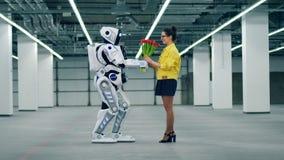 En dam får blommor från en högväxt cyborg stock video