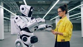 En dam fungerar en cyborg med en minnestavla arkivfilmer