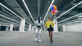 En dam med ballonger går med en cyborg längs korridoren stock video