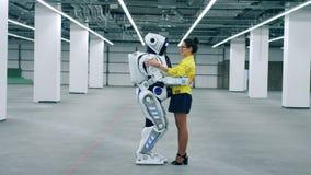 En dam rymmer en cyborg och talar till det lager videofilmer