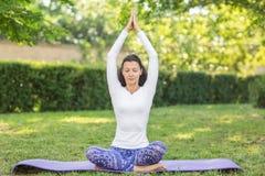 En dam rymmer händer över hennes huvud och mediterar på en matt purpurfärgad yoga Skönheten är iklädd en tröja och damasker Royaltyfri Fotografi