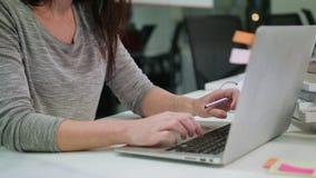 En dam Sitting i kontorsmaskinskrivningen på en bärbar dator royaltyfria foton