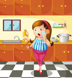 En dam som rymmer en orange fruktsaft inom köket Arkivbild