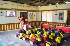 En damlärare som tar audivisuell grupp av dagisbarn i ett rum royaltyfria bilder