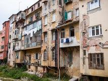 En degraderad grannskap som förbiser en liten vik Arkivbild