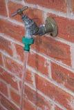 En dehors du robinet, l'eau fonctionnant avec le connecteur de tuyau adapté Photo stock
