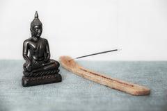 En dekorativ staty av Buddha, Buddha på bakgrunden av rökelse, Siddhartha Gautama har nått insikt symbol arkivfoton