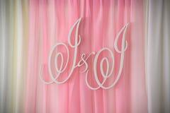 En dekorerad brölloptabell med lila- och rosa färgbollar och ett tecken med bokstäver I och I royaltyfri fotografi