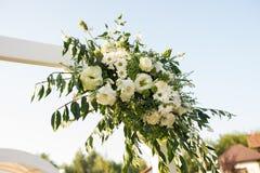 En del av den härliga bröllopbågen med ny vita blommor och grönska i trädgården Arkivfoto