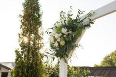 En del av den härliga bröllopbågen med ny vita blommor och grönska i trädgården Arkivbild