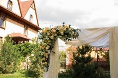 En del av den härliga bröllopbågen med ny vita blommor och grönska i trädgården Arkivfoton