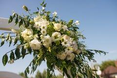 En del av den härliga bröllopbågen med ny vita blommor och grönska i trädgården Royaltyfri Foto