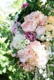 En del av den härliga bröllopbågen med rosa färgblommor och grönska i trädgården Fotografering för Bildbyråer