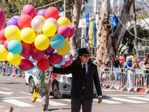 En deltagare i den ettårig växtAdloyada karnevalet går med en stor grupp av uppblåsta kulöra bollar i Nahariyya, Israel Royaltyfria Bilder