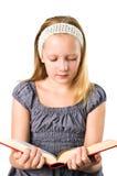 En deltagaretonåringflicka som läser en bok Arkivfoton