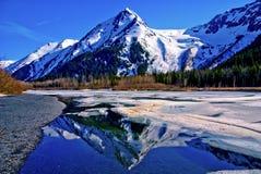 En delvist fryst sjö med bergskedja reflekterad i det delvist fryste vattnet av en sjö i den stora alaskabo vildmarken. Arkivfoto