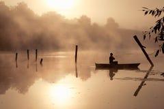 En dimmig morgon vid sjön Liten fiskebåt på sjön royaltyfri foto