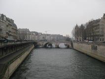 En dimmig sikt in mot en bro över floden Seine, Paris arkivbilder
