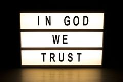En dios confiamos en el tablero de la muestra de la caja de luz stock de ilustración