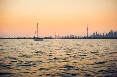 En disig sommarsolnedgång över den Toronto hamnen arkivbild