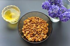 En djup plattabunke med flingor av havremjölet och honung på en mörk bakgrund med blommor Riktig n?ring f?r sund frukost arkivbild