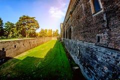 En djup vallgrav och en hög vägg av en forntida fästning Castello Sforzesco Sforza rockerar i Milan Fotografering för Bildbyråer