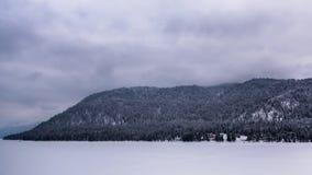 En djupfryst bergsjö i dimman arkivfilmer
