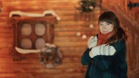 En djupfryst flicka i tumvanten värme sig på bakgrunden av ett träsagahus Tema för jul och för nytt år arkivfilmer