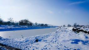 En djupfryst flod i fångenskap nära förkylningen bluen clouds skysnowsticken Jag gillar att gå på en djupfryst flod Åka skridskor Arkivbilder