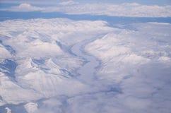 En djupfryst flodspring till och med is och insnöade Alaska Arkivfoto