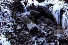 En djupfryst ström i vinter Djupfryst bäck med istappen i en grotta Royaltyfri Bild