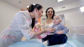 En doktor använder hennes stetoskop på ett litet barn lager videofilmer