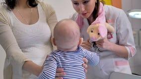 En doktor distraherar ett litet barn med ett luxuöst svin lager videofilmer