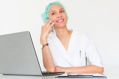 En doktor With för ung kvinna en bärbar dator i hennes kontor som talar på telefonen Fotografering för Bildbyråer