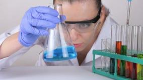 En doktor för ung kvinna rör flytanden i en flaska lager videofilmer