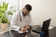 En doktor i ett vitt lag i ett kontor för doktors` s sitter på en tabell, och påfyllningslegitimationshandlingar manipulerar kont Arkivbild