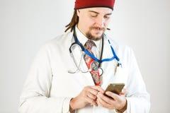 En doktor med dreadlocks och ett skägg rymmer en smartphone i hans händer, en stetoskop, och ett emblem hänger runt om hans hals royaltyfri fotografi