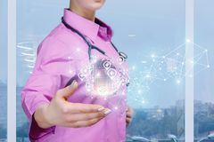 En doktor med ett digitalt system av medicinska symboler, jordklotet och trådlösa anslutningar som hänger ovanför hennes hand royaltyfria foton