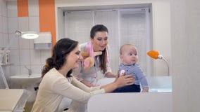 En doktor och modern ser ner på ett litet barn arkivfilmer