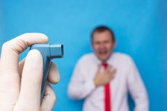 En doktor rymmer en astmainhalator med salbutamol, i bakgrunden är en man, som kväv på astma, bronchodilator royaltyfri fotografi