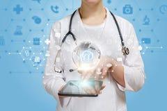 En doktor som använder hennes grej för att arbeta med det online-globala medicinska systemet fotografering för bildbyråer