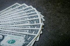 En dollar sedlar på en svart tabell Kontanta pengaramerikandollar för prydnadpapper för bakgrund geometrisk gammal tappning Lens  Arkivbild