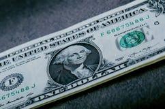 En dollar sedlar på en svart tabell Kontanta pengaramerikandollar för prydnadpapper för bakgrund geometrisk gammal tappning Lens  Royaltyfri Foto