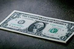 En dollar sedlar på en svart tabell Kontanta pengaramerikandollar för prydnadpapper för bakgrund geometrisk gammal tappning Lens  Arkivfoto
