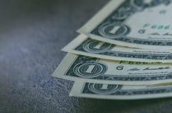 En dollar sedlar på en svart tabell Kontanta pengaramerikandollar för prydnadpapper för bakgrund geometrisk gammal tappning Lens  Royaltyfria Foton