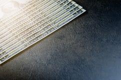 En dollar sedlar på en svart tabell Kontanta pengaramerikandollar för prydnadpapper för bakgrund geometrisk gammal tappning Lens  Fotografering för Bildbyråer