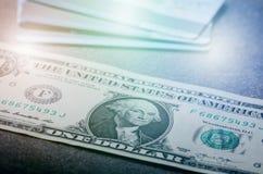En dollar sedlar på en svart tabell med kreditkortar Kontanta pengaramerikandollar för prydnadpapper för bakgrund geometrisk gamm Arkivbilder