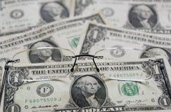 En dollar sedlar som en bakgrund och exponeringsglas arkivfoton
