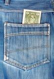 En dollarräkning som klibbar i bakfickan av jeans Arkivbilder